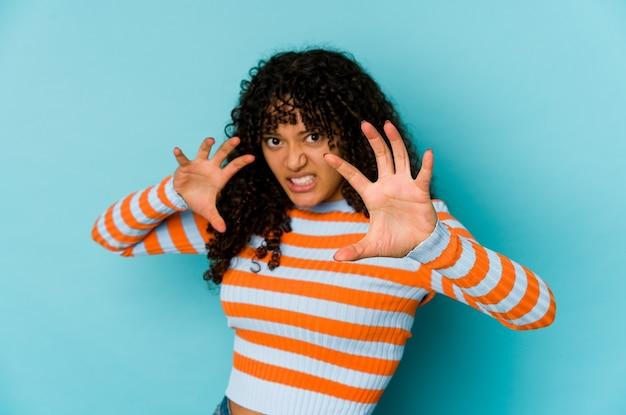 Giovane donna afroamericana afro isolato sconvolto urlando con le mani tese.