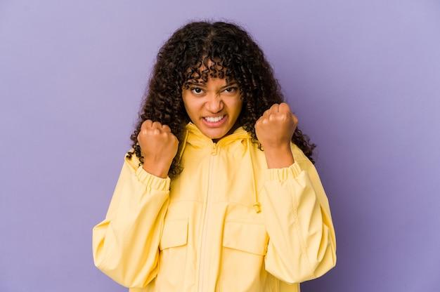 Giovane donna afroamericana afro sconvolta urlando con mani tese.