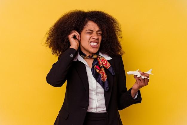 Giovane hostess afroamericana che tiene un piccolo aereo isolato su sfondo giallo che copre le orecchie con le mani.