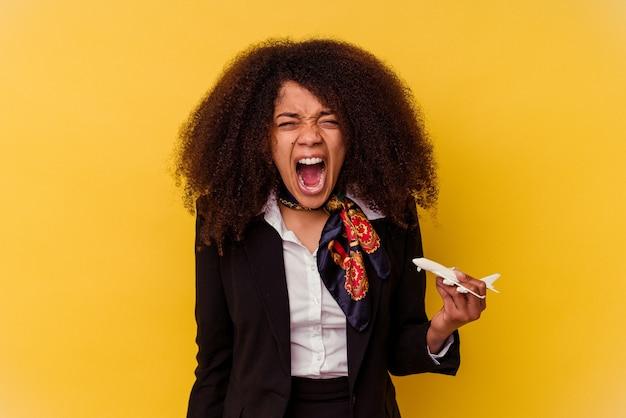 Giovane hostess afroamericana che tiene un piccolo aereo isolato su sfondo giallo urlando molto arrabbiato e aggressivo.