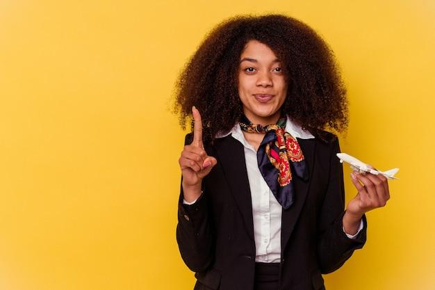 Giovane hostess afroamericana che tiene un piccolo aereo isolato su sfondo giallo che mostra il numero uno con il dito.