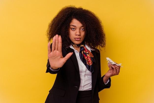 Giovane hostess afroamericana che tiene un piccolo aereo isolato su sfondo giallo in piedi con la mano tesa che mostra il segnale di stop, impedendoti.