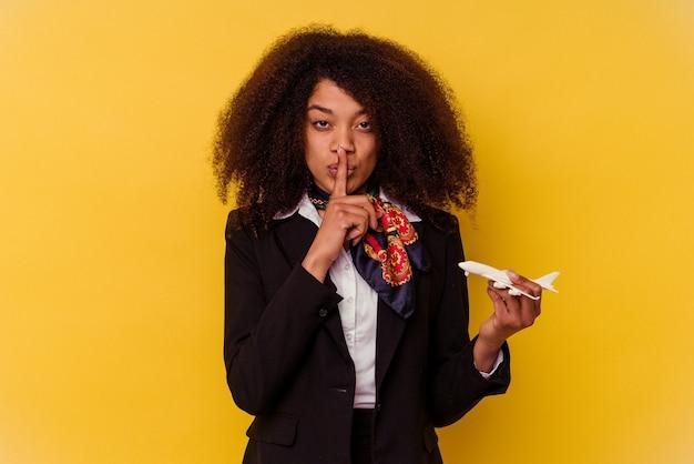 Giovane hostess afroamericana che tiene in mano un piccolo aereo isolato su giallo mantenendo un segreto o chiedendo silenzio.