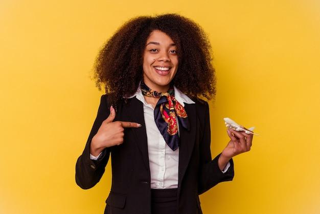 Giovane hostess afroamericana che tiene un piccolo aereo isolato sulla persona gialla che indica a mano uno spazio copia camicia, orgoglioso e sicuro