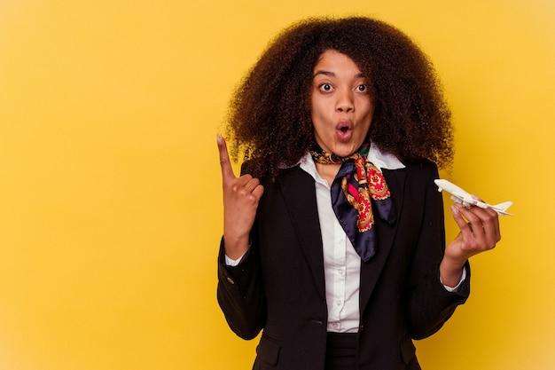 Giovane hostess afroamericana che tiene un piccolo aereo isolato sul giallo che punta al lato