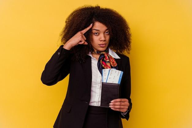 Giovane hostess afroamericana in possesso di un biglietto aereo isolato su sfondo giallo che punta il tempio con il dito, pensando, concentrato su un compito.