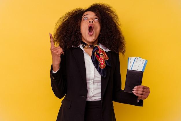 Giovane hostess afroamericana in possesso di un biglietto aereo isolato su sfondo giallo rivolto verso l'alto con la bocca aperta. Foto Premium
