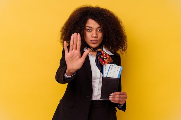 Giovane hostess afroamericana in possesso di un biglietto aereo isolato su giallo in piedi con la mano tesa che mostra il segnale di stop, impedendoti.