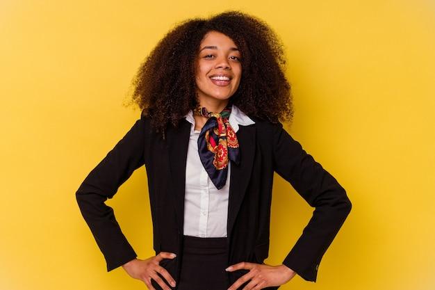 Giovane hostess afroamericana isolata su sfondo giallo sicura di tenere le mani sui fianchi.