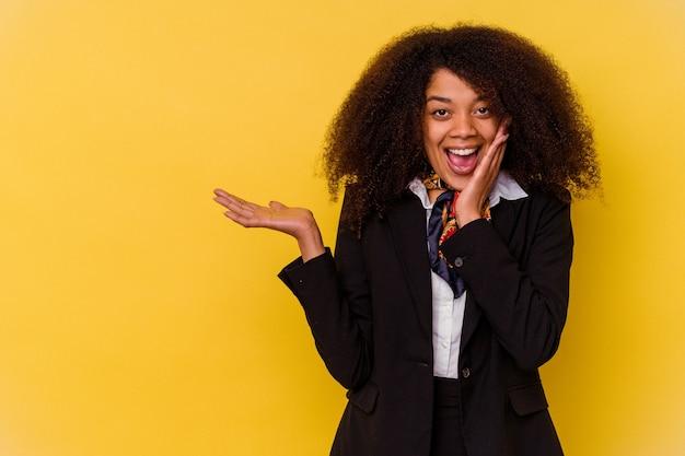La giovane hostess afroamericana isolata su sfondo giallo tiene lo spazio della copia su un palmo, tenere la mano sulla guancia. stupito e deliziato.