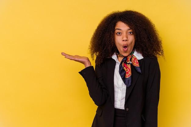 La giovane hostess afroamericana isolata su sfondo giallo ha colpito lo spazio della copia della holding sul palmo.