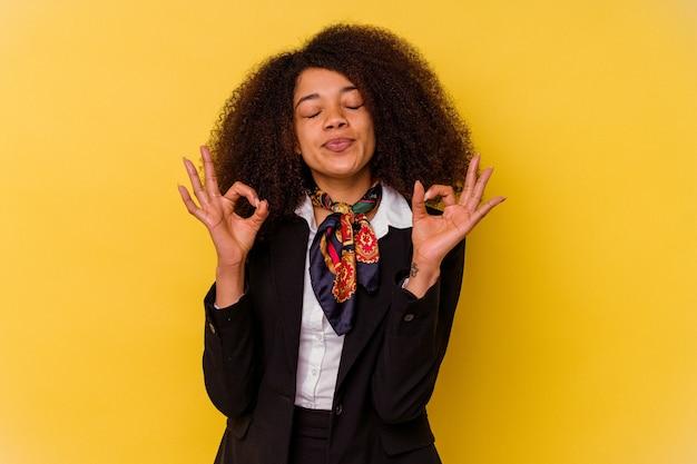 La giovane hostess afroamericana isolata su sfondo giallo si rilassa dopo una dura giornata di lavoro, sta eseguendo yoga.