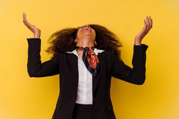 Giovane hostess afroamericana isolata su sfondo giallo che urla al cielo, alzando lo sguardo, frustrata.
