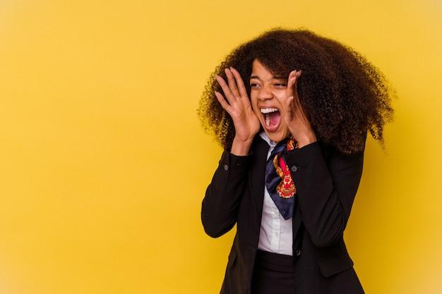 La giovane hostess afroamericana isolata su sfondo giallo grida forte, tiene gli occhi aperti e le mani tese.