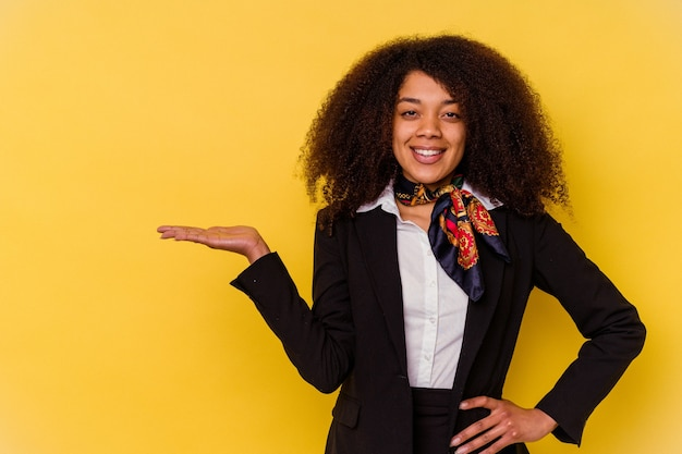 Giovane hostess afroamericana isolata su sfondo giallo che mostra uno spazio di copia su un palmo e tiene un'altra mano sulla vita.