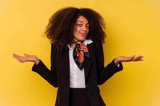 Giovane hostess afroamericana isolata su giallo dubitando e scrollando le spalle nel gesto interrogativo.