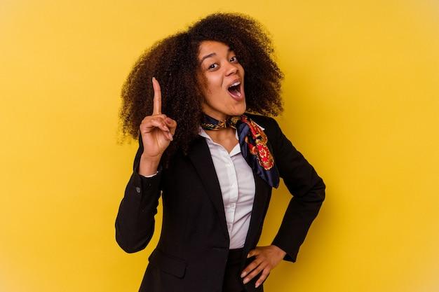 Assistente di volo afroamericano giovane isolato su giallo che ha un'idea, concetto di ispirazione.
