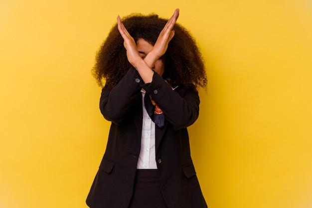 Giovane hostess afroamericana isolata sul giallo che tiene due braccia incrociate, concetto di negazione.