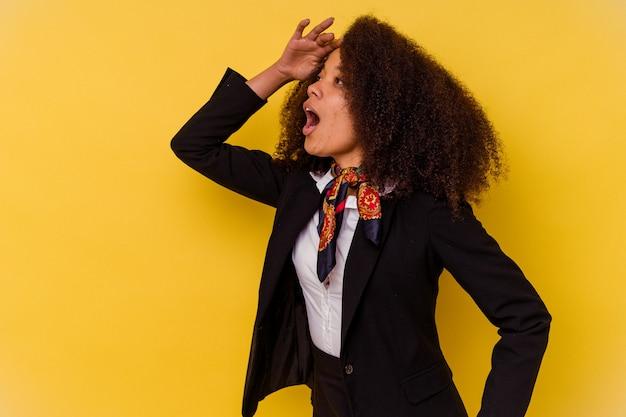 Giovane hostess afroamericana isolata sul giallo che guarda lontano tenendo la mano sulla fronte.