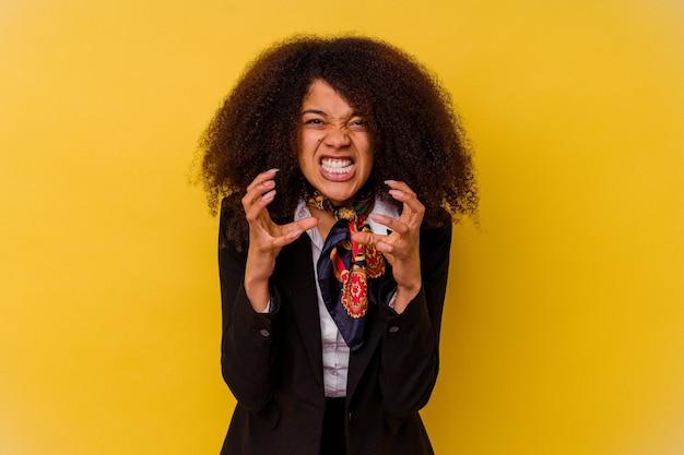 Assistente di volo dell'afroamericano giovane isolata sul ribaltamento giallo che grida con le mani tese.