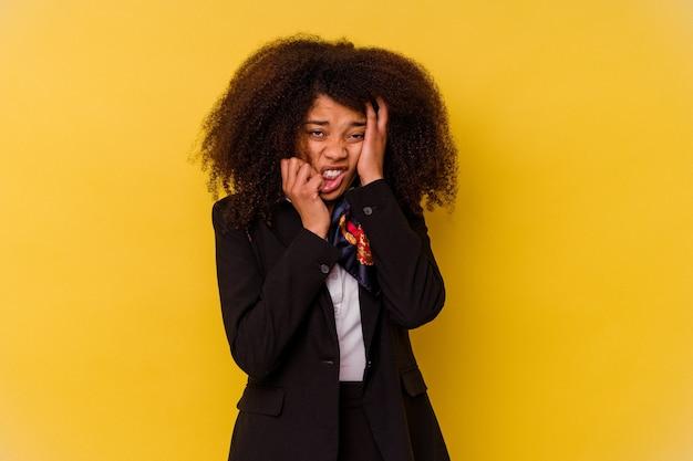 Giovane hostess afroamericana isolata sul giallo che piagnucola e piange sconsolatamente.