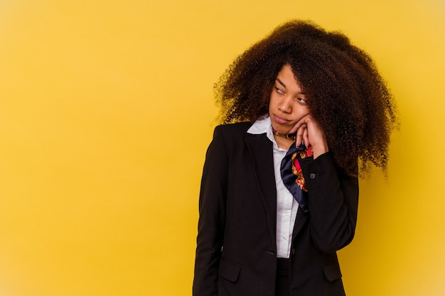 Giovane hostess afroamericana isolata sul giallo che si sente triste e pensieroso, guardando lo spazio della copia.