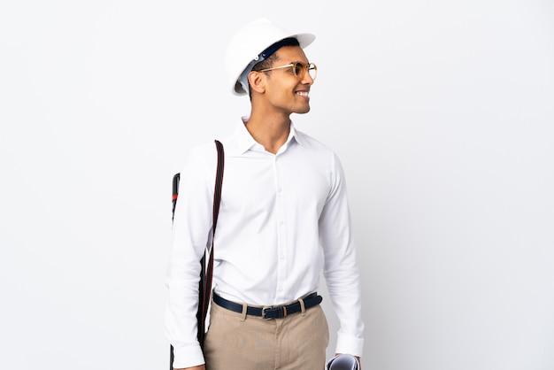 Giovane uomo afroamericano dell'architetto sopra la parete bianca isolata