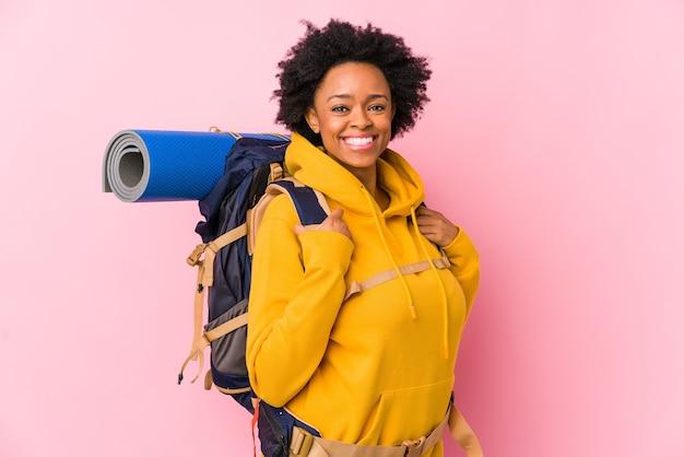 La giovane donna afroamericana del viaggiatore con zaino e sacco a pelo ha isolata felice, sorridente e allegra.