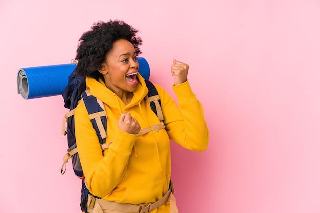 Giovane donna afro-americana con zaino e sacco a pelo isolata pugno di sollevamento dopo una vittoria, concetto di vincitore
