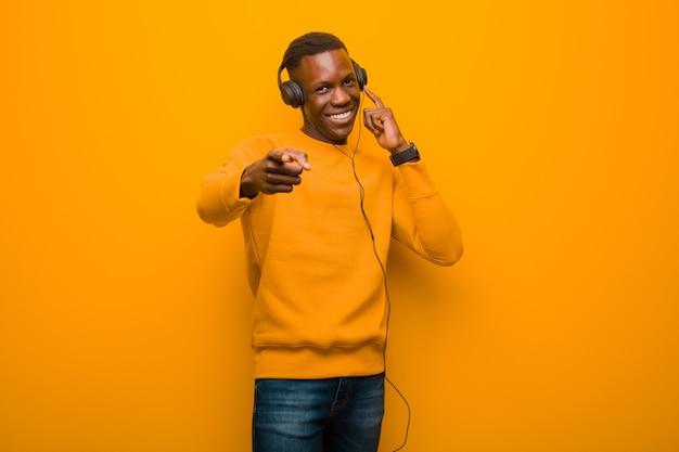 Giovane uomo di colore afroamericano contro la parete arancio con le cuffie