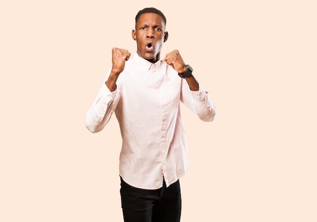 Giovane uomo di colore afroamericano che celebra un incredibile successo come un vincitore, apparendo eccitato e felice di dire prendi quello! contro il muro beige