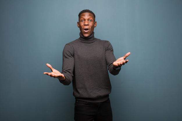 Giovane uomo di colore afroamericano che si sente estremamente scioccato e sorpreso, ansioso e in preda al panico, con uno sguardo stressato e inorridito sul muro del grunge