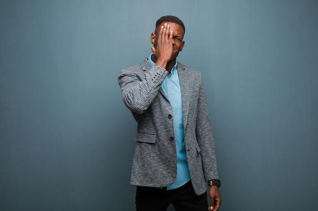 Giovane afroamericano uomo nero che sembra assonnato, annoiato e sbadigliare, con un mal di testa e una mano coning metà del viso sulla parete del grunge