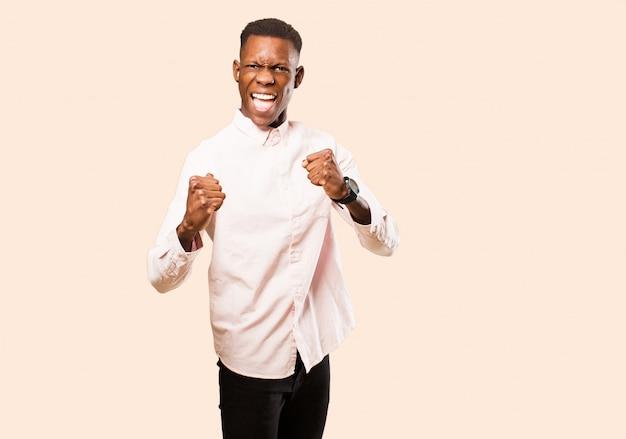 Il giovane uomo di colore afroamericano che grida aggressivamente con un'espressione arrabbiata o con i pugni serrati celebra il successo sopra la parete beige