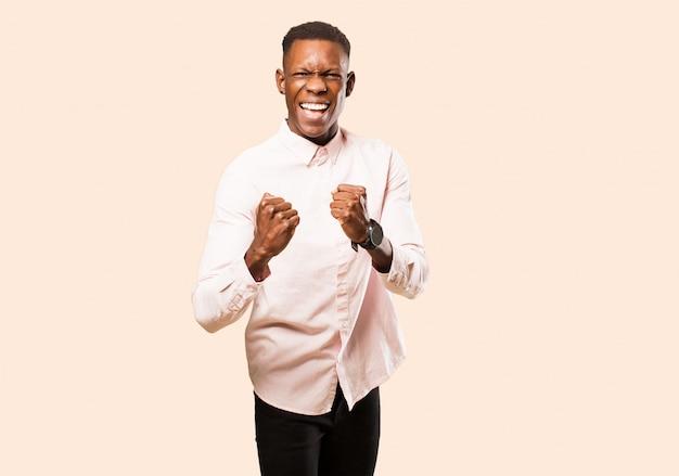 Giovane uomo di colore afroamericano che grida trionfalmente, ridendo e sentendosi felice ed eccitato mentre celebra il successo contro la parete beige