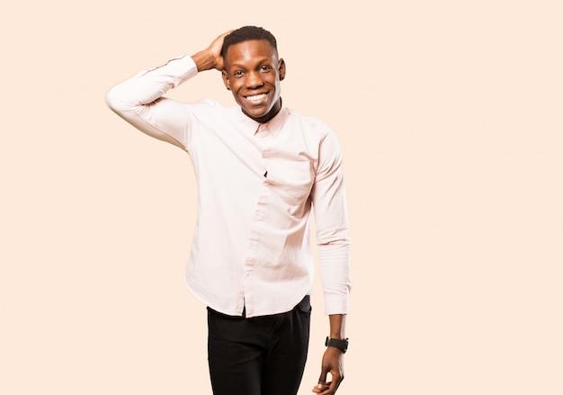 Giovane uomo di colore afroamericano che sorride allegramente e con indifferenza, prendendo a braccetto con uno sguardo positivo, felice e sicuro contro la parete beige