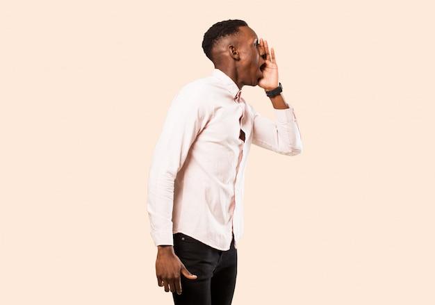 Giovane uomo di colore afroamericano che urla ad alta voce e rabbiosamente per copiare lo spazio sul lato, con la mano accanto alla bocca contro la parete beige