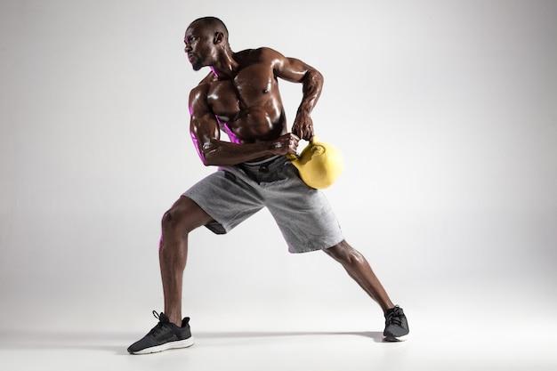 Giovane bodybuilder afroamericano che si allena su sfondo grigio