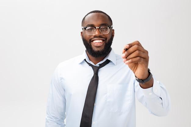Giovane uomo di affari dell'afroamericano che scrive qualcosa sul bordo di vetro con un indicatore