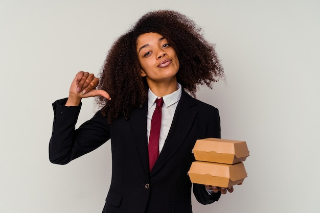 La giovane donna d'affari afroamericana che tiene un hamburger isolato su sfondo bianco si sente orgogliosa e sicura di sé, esempio da seguire.