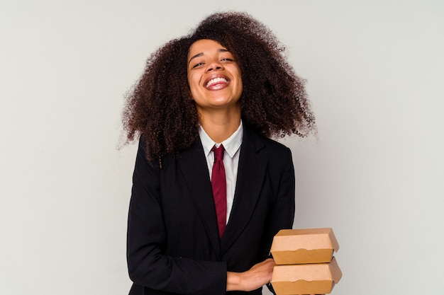 Giovane donna afroamericana di affari che tiene un hamburger isolato su fondo bianco che ride e che si diverte.