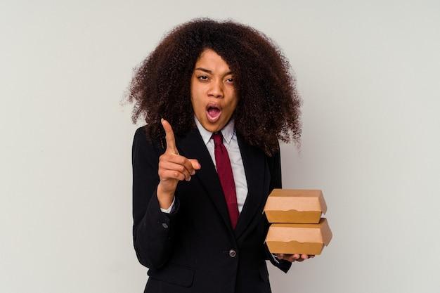 Giovane donna afroamericana di affari che tiene un hamburger isolato su bianco che ha un'idea, concetto di ispirazione.