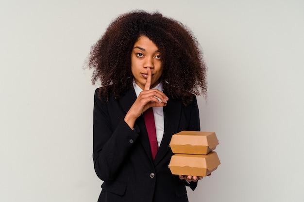 Giovane donna d'affari afroamericana che tiene un hamburger isolato su bianco mantenendo un segreto o chiedendo silenzio.