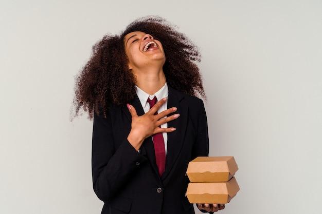 La giovane donna afroamericana di affari che tiene un hamburger isolato su bianco ride ad alta voce tenendo la mano sul petto.
