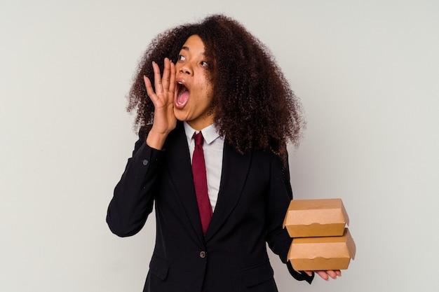 Giovane donna afroamericana di affari che tiene un hamburger isolato su bianco che grida e che tiene il palmo vicino alla bocca aperta.