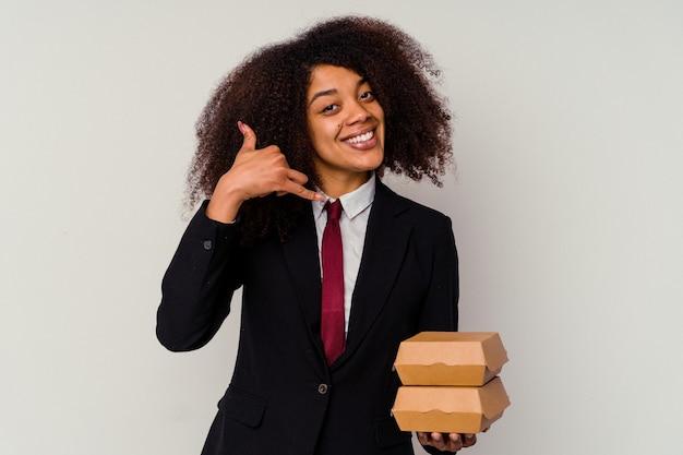 Giovane donna afroamericana di affari che tiene un hamburger isolato su bianco che mostra un gesto di chiamata di telefono cellulare con le dita.
