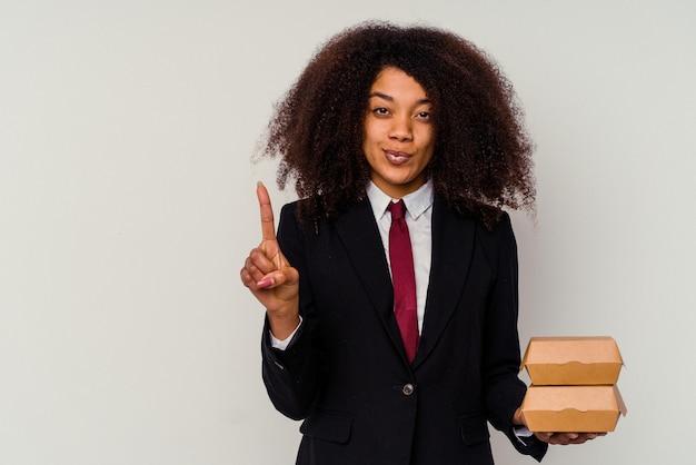 Giovane donna d'affari afroamericana che tiene un hamburger isolato su bianco che mostra il numero uno con il dito.