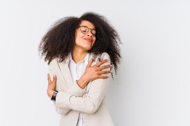 Giovani abbracci afroamericani della donna di affari, sorridenti spensierati e felici.
