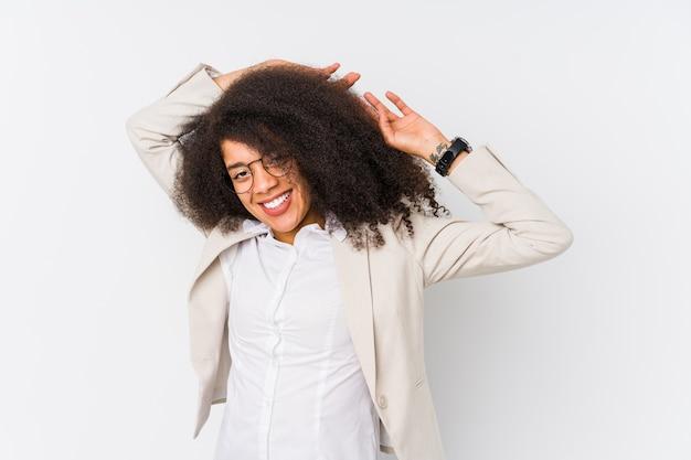 Giovane donna d'affari afro-americana che allunga le braccia, posizione rilassata.