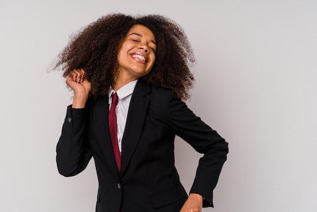 Giovane donna d'affari afroamericana che indossa un abito isolato su sfondo bianco ballare e divertirsi.